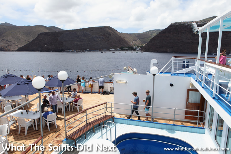 Passengers gather on the Sun Deck to watch the departure from James Bay.