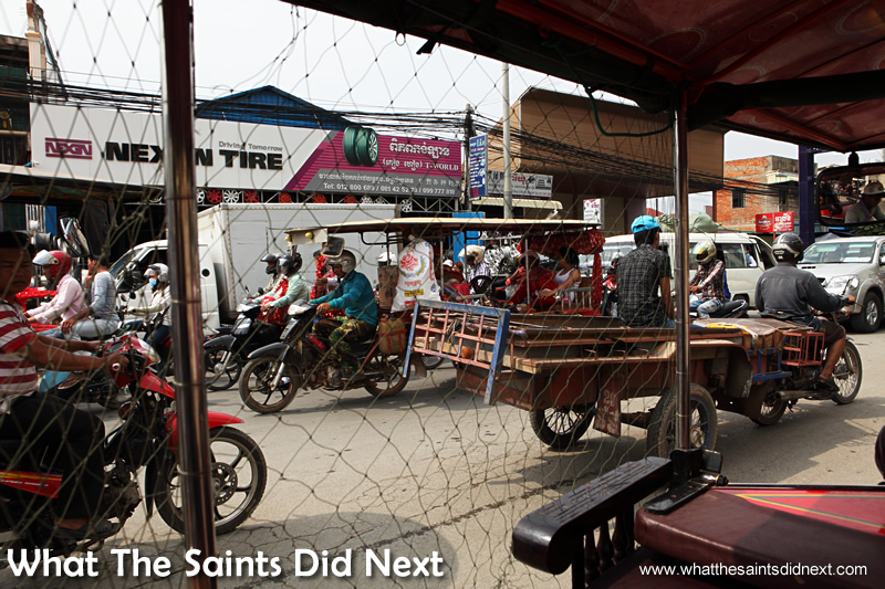 The bedlam of the Phnom Penh traffic viewed up close from inside a tuk tuk.
