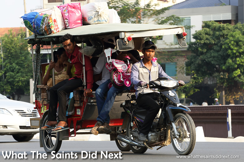 The flat terrain allows the mopeds to pull all manner of heavily laden trailers in Cambodia.