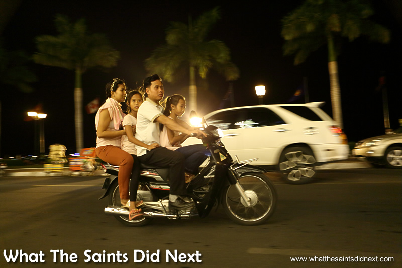 A family out for the night, cruising through the Riverside in Phnom Penh.