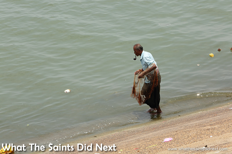 A man fishing in the river below the shrine.