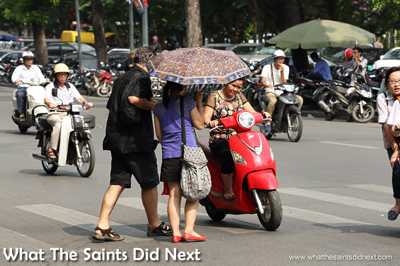 This moped driver passed so close to this couple the driver had to duck under the umbrella.
