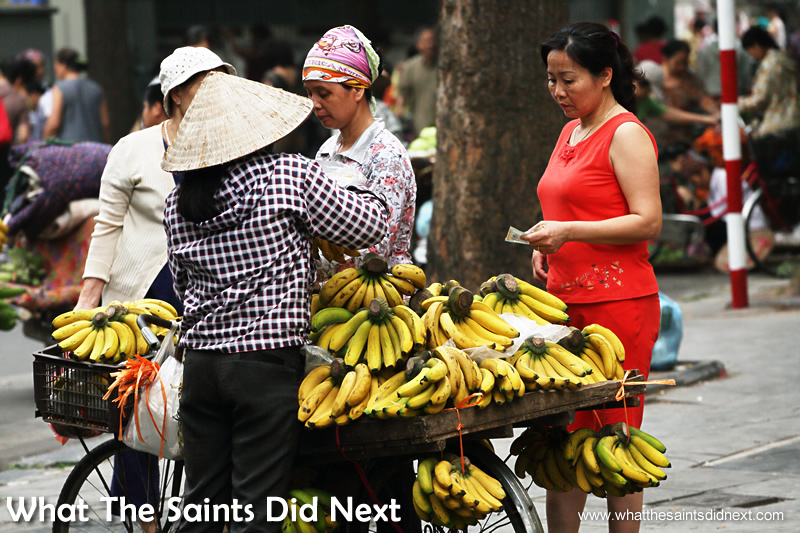 A banana seller is out making a sale first thing in the morning.