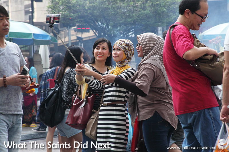 Three young friends pose for a selfie at the Erawan Shrine, Bangkok.