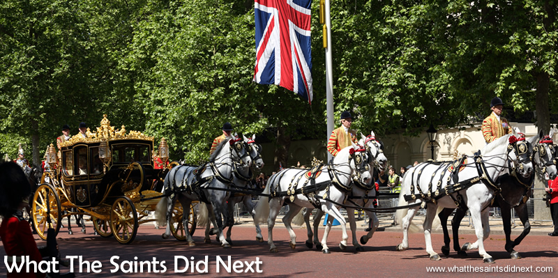 The Queen's carriage pulled by six white horses, travelling up the Mall.