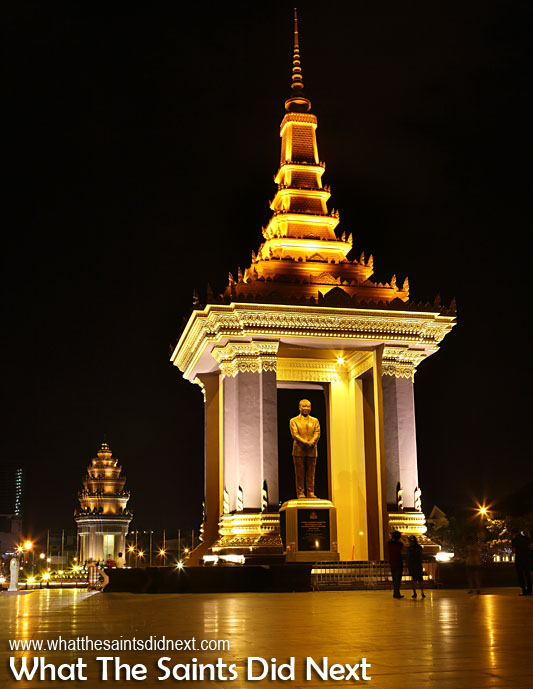 King Norodom Sihanouk's statue in Neak Banh Teuk Park at night, Phnom Penh, Cambodia. Victory Monument can be seen in the background. Cambodian Independence Day celebrations will be focused around this park.