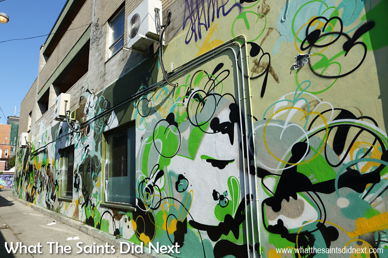 An entire alley wall covered in a camouflage-like design. Alleys in this part of Toronto have become inviting art galleries.