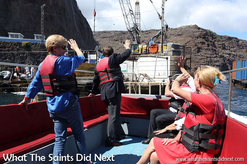 Goodbye St Helena. Governor Mark Capes and Mrs Tamara Capes wave goodbye as the launch pulls away from the wharf steps. 18 March, 2016.