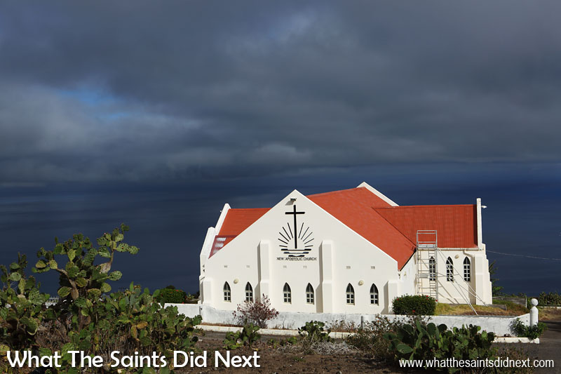 16 Pictures Celebrating St Helena Day 2016. The New Apostolic Church in Half Tree Hollow catches a spotlight of sunshine while dark storm clouds gather around the rest of the island.