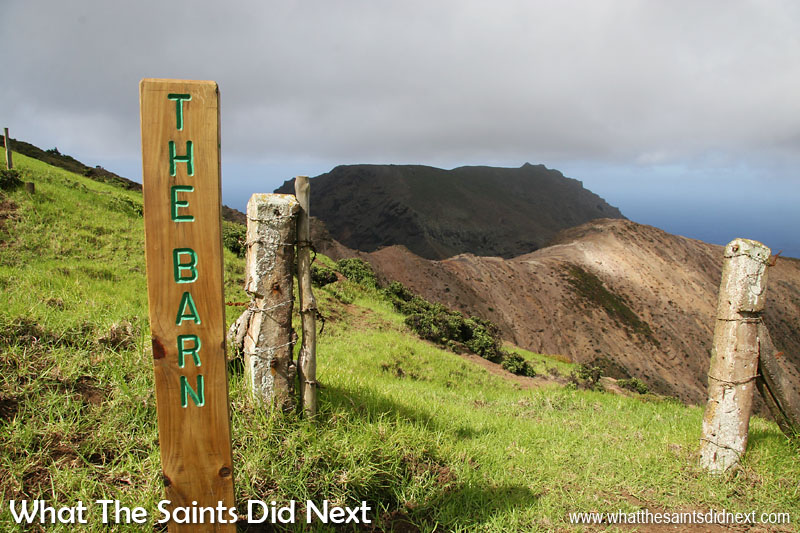 The Barn, St Helena. This marker post can be found on the edge of Deadwood Plain, at the point where the trail heads off the grassy plain and down over the hill, through the furze bushes. The dark hulk of the Barn itself can be seen in the distance.