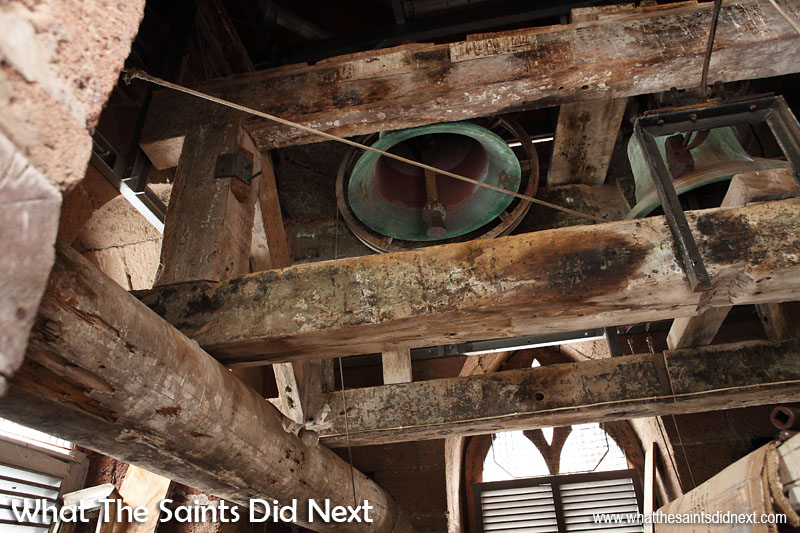 The clock bell (right) and the manual church service bell (left) installed at the top of the tower, above the clock and directly under the spire. The large round beams are believed to have previously been sailing ship masts. St James Church clock tower, Jamestown, St Helena.