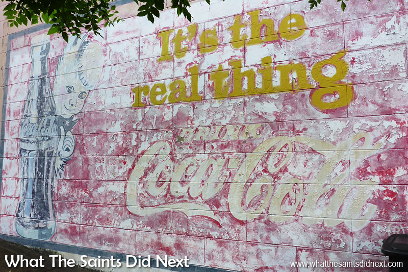 It's the real thing.  Coca-Cola Sprite Boy.   Vicksburg, MS. Ghost signs of the US. Don't know how old this sign is but the mischievous looking Sprite Boy was used as a marketing mascot in the 40s and 50s.  Unfortunately the paint is peeling and the sign appears to have not taken kindly to restoration work.  Coincidently Coca-Cola was first bottled in Vicksburg back in 1891.