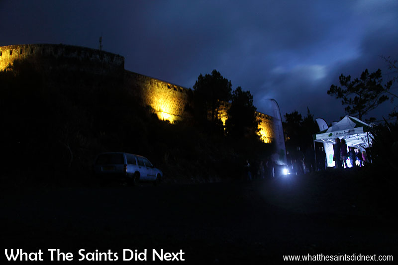 The view from up close. Guests at the High Knoll car park gaze upwards as the first sequence of colours illuminates the old stone walls. Lighting High Knoll Fort, St Helena.