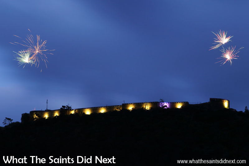 Opening night firework display. Fireworks are launched from both ends of the fort, the loud 'bangs' echoing up and down the valleys. Lighting High Knoll Fort, St Helena.