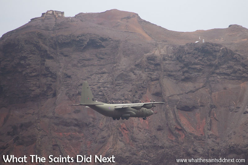 The low profile camouflage paint job almost hides the RAF C-130J Hercules against the King and Queen headland, topped by Prosperous Bay Plain House. RAF, C-130J Hercules at St Helena Airport.